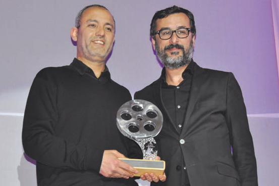 Mohamed Moftakir, recevant le trophée des mains de Salim Cheikh, directeur général de 2M.