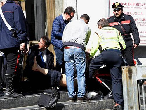 Des gens aident un blessé par un homme qui a ouvert le feu jeudi matin au tribunal de Milan, provoquant la mort de trois personnes, dont un juge afp.com - OLIVIER MORIN