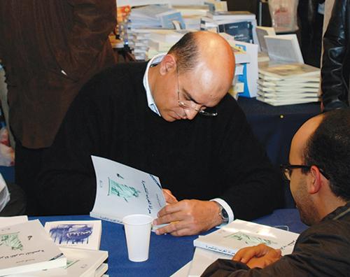Hassan Aourid dédicaçant un de ses livres. - © Photo : MHI