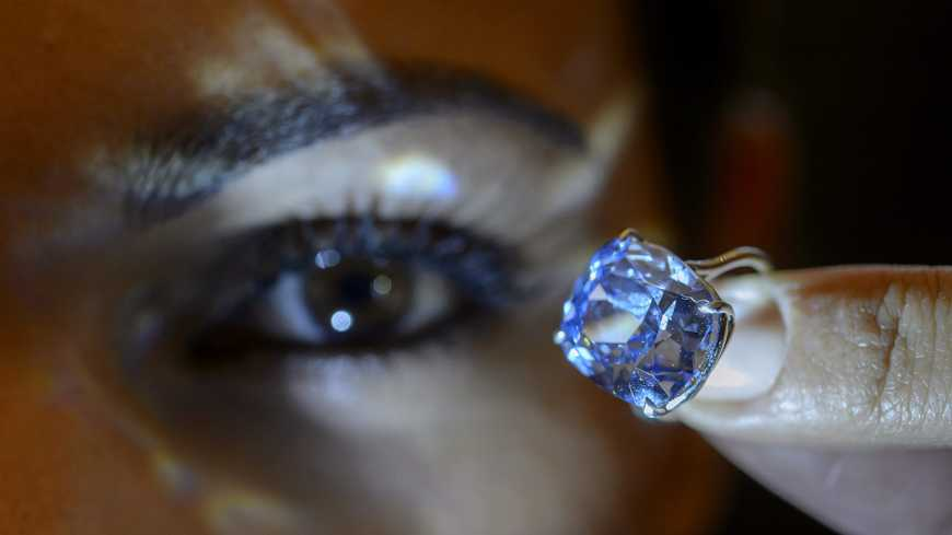 epa05010385 A Sotheby's employee displays the rare Blue Moon Diamond during a preview at the Sotheby's, in Geneva, Switzerland, 04 November 2015. The 12.03 carat blue diamond is the largest cushion shaped fancy vivid blue diamond to ever appear at auction. It is estimated to sell between 35-55 million US dollars. The auction will take place in Geneva, on 11 November.  EPA/MARTIAL TREZZINI (MaxPPP TagID: epalive892620.jpg)